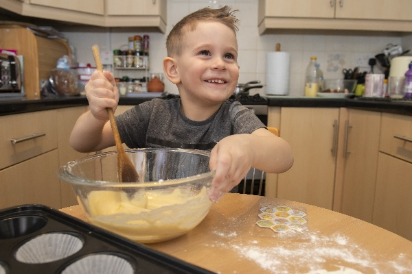 Young boy making cupcakes