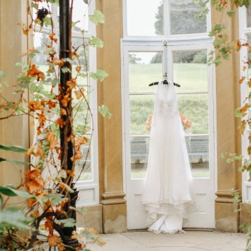 Brides dress hung up with decorations around