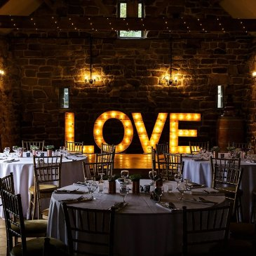 Dining tables with big lit up love lights