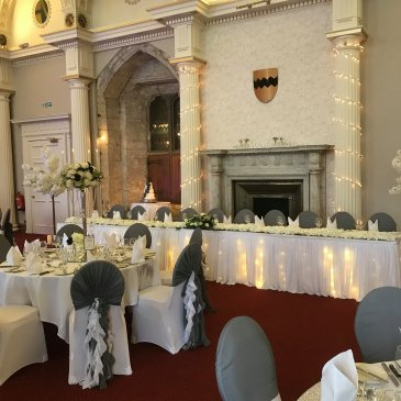 Tables and chairs with head table and fairy lights on pillars