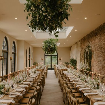 Long hall with hanging floral baskets and tables and chairs laid out for wedding dinner
