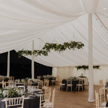 Marquee with fairy lights and tables and chairs set for dinner