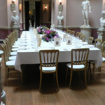 Long table with statues in background and chairs with floral centre pieces