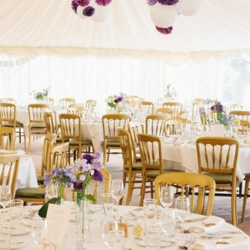 Tables and chairs all set out in large marquee