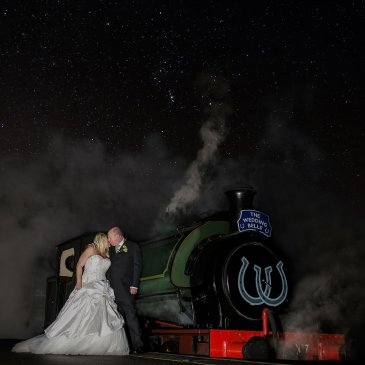 Bride and groom on edge of train under starry sky