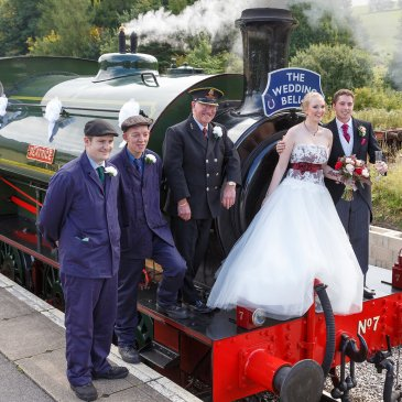 Bride and groom with train workers waiting on platform