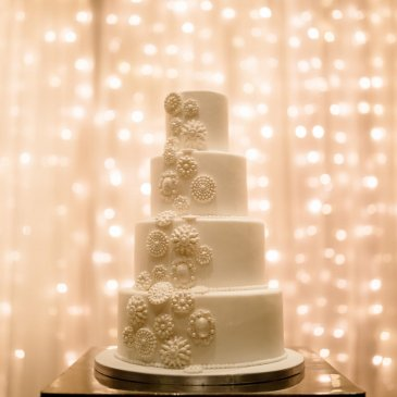 Beautiful and large wedding cake with fairy light backdrop