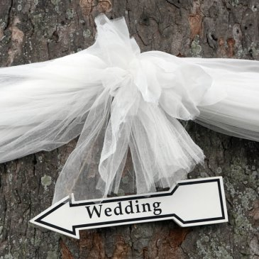 Tree wrapped with ribbon and arrow pointing towards wedding venue
