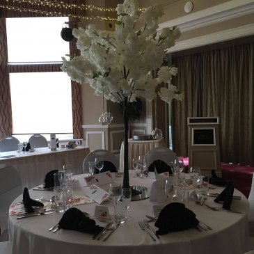 Seats and table set out for wedding meal with floral centre piece