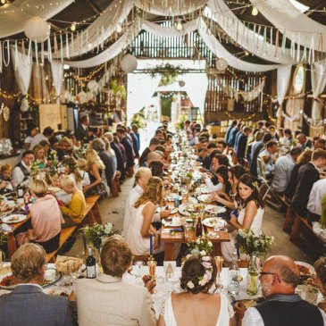 Large gathering of wedding guests in grand barn