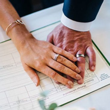 Bride and groom holding hands while signing marriage certificate