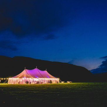 Wedding marquee glowing in field in the middle of the night