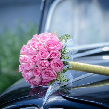 Bouquet of pink flowers on hood of fancy car