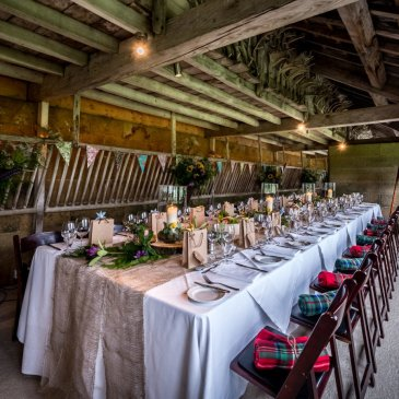 Long table with chairs surrounding and floral centrepieces