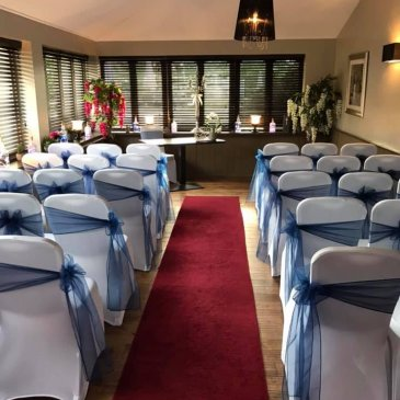 Seats set out on each side of aisle facing wedding ceremony
