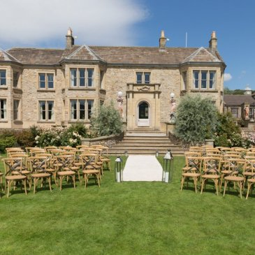 Chairs laid out each side of aisle outdoors for wedding ceremony