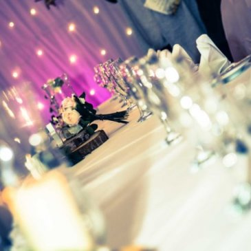 Table set out with floral centre piece and fairy light backdrop