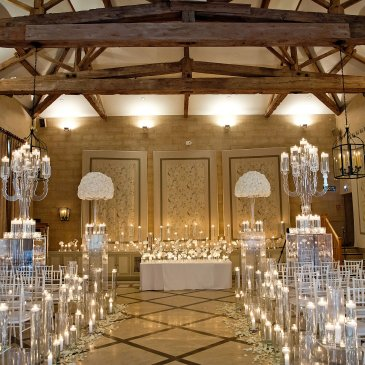 Large hall with wooden ceiling beams and floral decorations and fairy lights