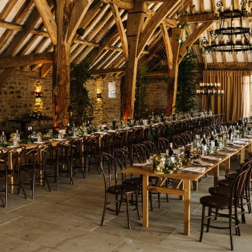 Large barn with rows of tables and chairs ready for wedding meal