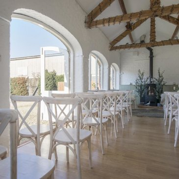 White chairs laid out in sun lit room with floral decorations