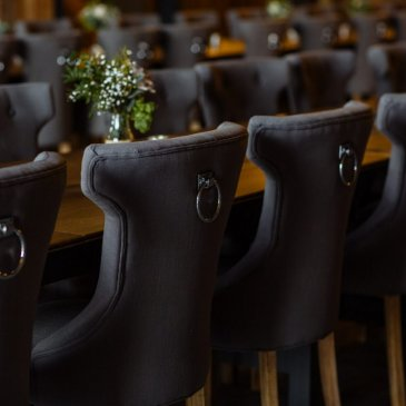 Dark chairs surrounding table with floral centre pieces