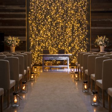 Chairs in rows on each side of aisle facing wedding ceremony