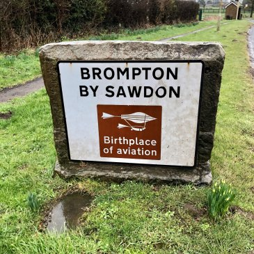Brompon-by-Sawdon village sign, funded by the village's 2003 '150' celebrations, which commemorated the 150th anniversary of Sir George Cayley's first human flying glider in 1853.