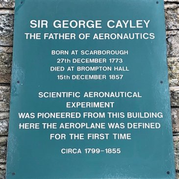 Photograph of a plaque located on the side of Sir George Cayley's workshop at Brompton Hall.