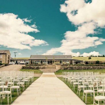 Chairs laid out facing towards wedding ceremony outside with beautiful sky