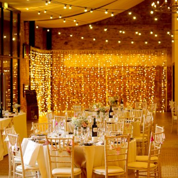 Tables and chairs set for wedding dinner in front of fairy lights
