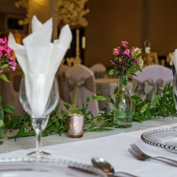 Floral decorations covering table with cutlery and plates on