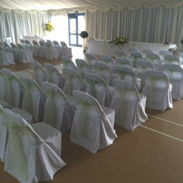 Chairs set out on each side of aisle facing wedding ceremony