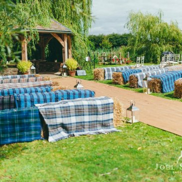 Hay bales laid out as seats on each side of aisle in outdoor wedding ceremony