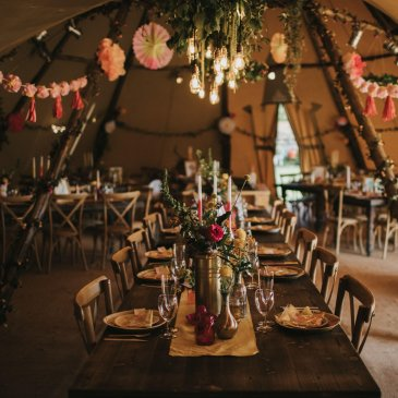 Long table with chairs each side and floral bunting overhead