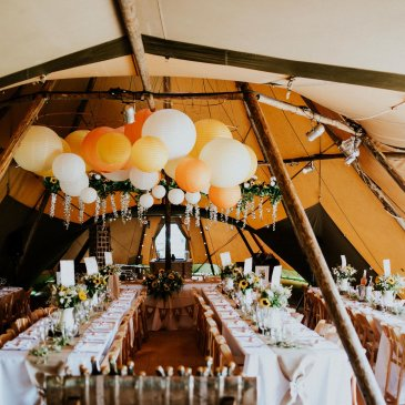 Long tables all along marquee for intimate wedding dinner