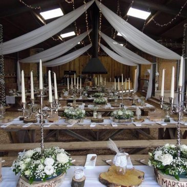 Open barn space laid out with table rows ready for wedding dinner