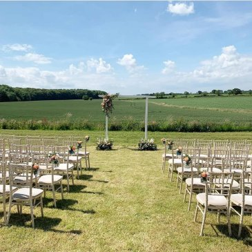 Seats each side of aisle facing wedding ceremony in outdoor wedding