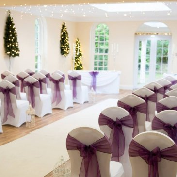 Chairs wrapped in ribbons on each side of aisle facing wedding ceremony