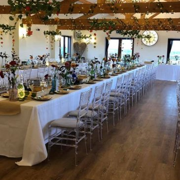 Long table set out with chairs each side ready for wedding meal