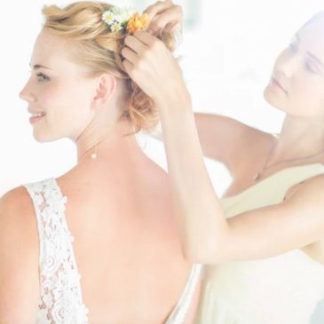 Bride's hair being tied by bride's maid