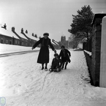 A child sledging down on a hill on Main Street, Coxwold