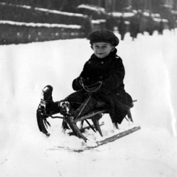 Child sitting on a sledge in Harlow Moor Drive, Harrogate