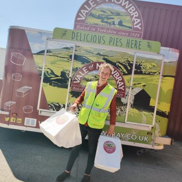Vale of Mowbray holding bags of pies