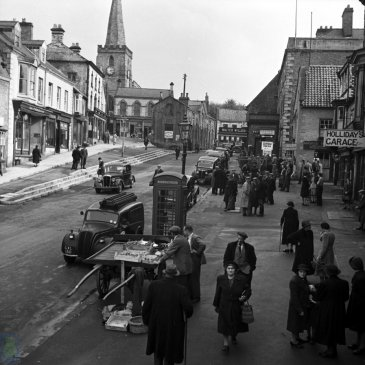 A view of the Market Place, Pickering during the Second World War.  Polish soldiers are standing outside Fred Pickup's butcher's shop  In front of the church are The Vaults. This building was used in the wartime as an air-raid shelter. It was later demolished in 1958