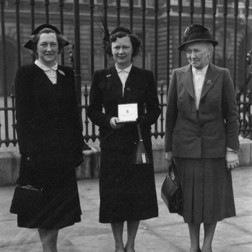 Photograph of Winifred Jacob Smith (centre) receiving her MBE at Buckingham Palace, with her sister Dorothy (left) and mother Dor