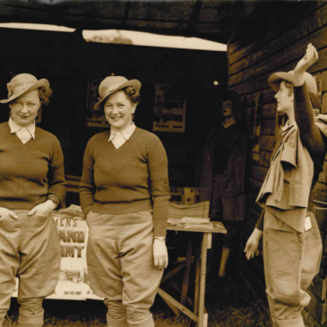 Photograph of Winifred (left) and her sister Dorothy (centre) at a Women's Land Army recruitment stand.