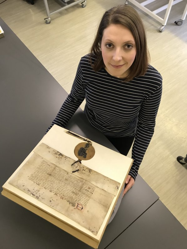 One of the many historic documents preserved by the County Record Office. Emily Ward, Record Assistant, with a grant bearing the great seal of Edward IV, 1478