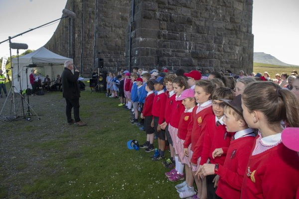 Pupils singing under the arches with Ian Bangay conducting