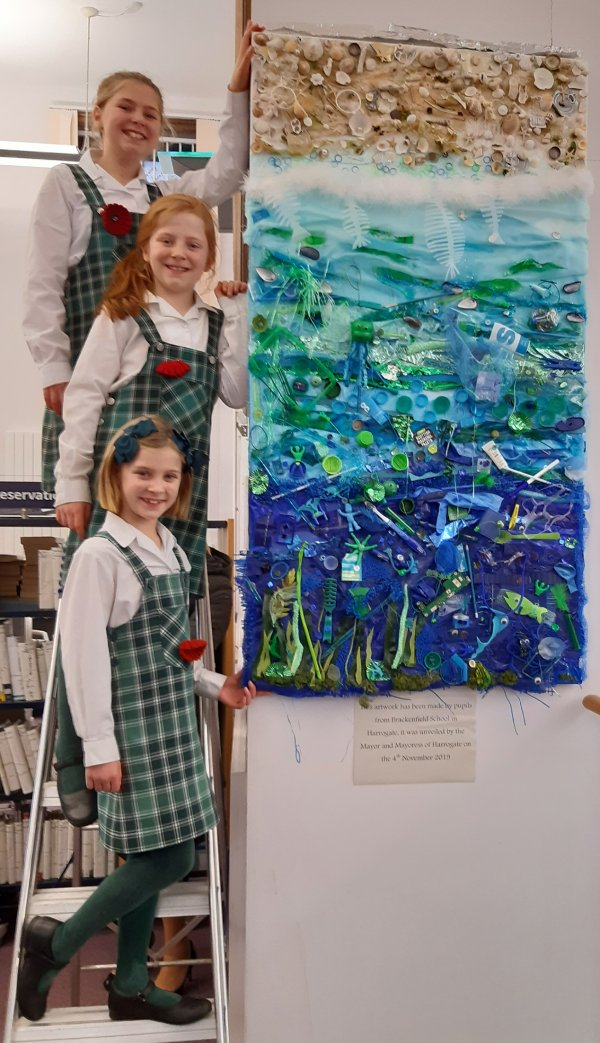 the sisters with their artwork at the library