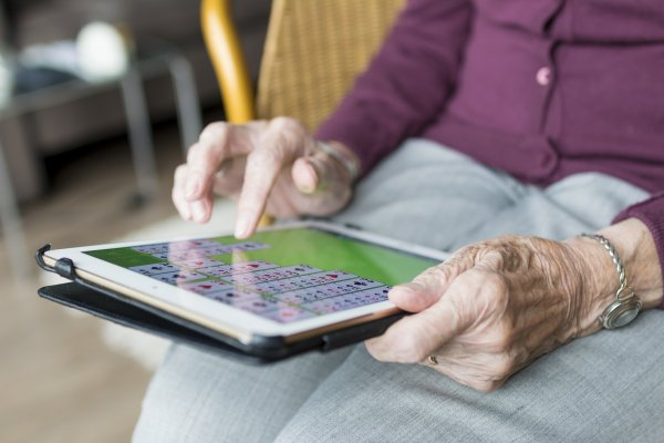 An elderly person using a tablet device.